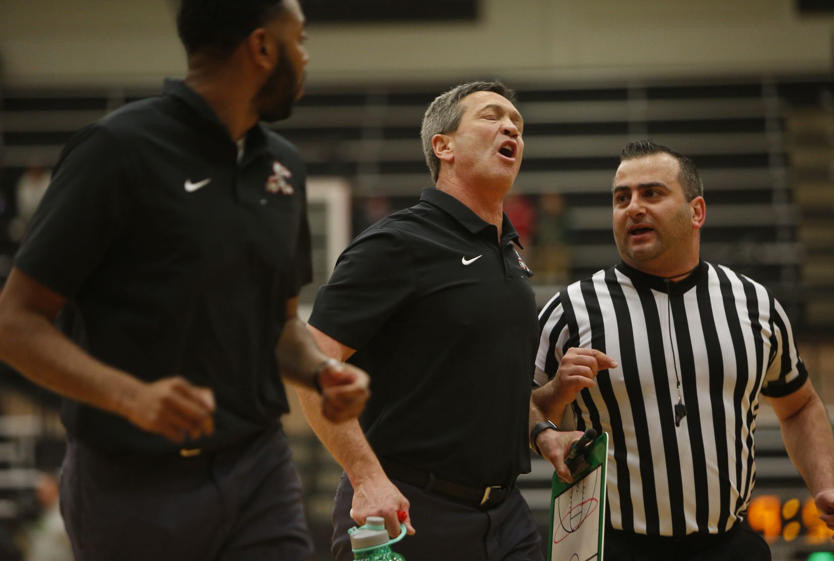 Waxahachie head coach Greg Gober, center, expresses his feelings on a first half call to a game official at halftime of their game against Coppell. Waxahchie won 62-50 to advance. The two teams played their Class 6A area-round boys basketball playoff game at Mansfield Timberview High School in Arlington on February 28, 2020.