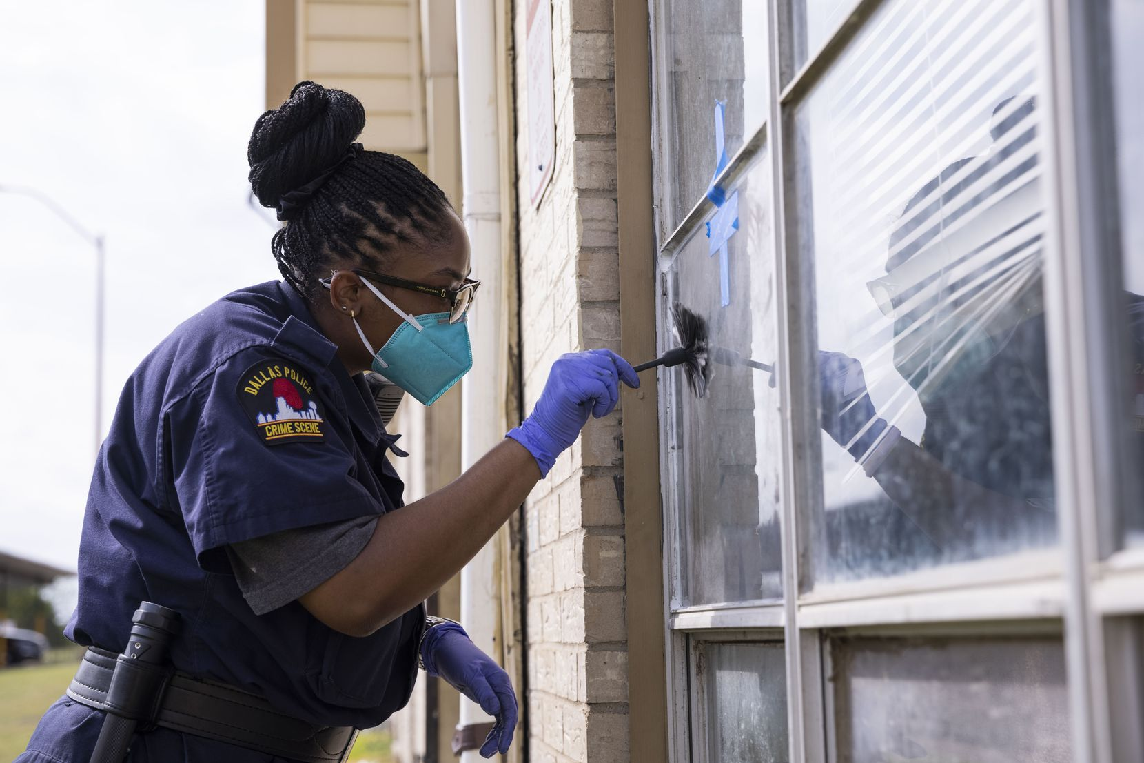 A Dallas Police crime scene investigator searches for prints outside of  Kayla and Daniel Aguilar's apartment on Wednesday, Oct. 13, 2021, at Highland Hills apartments in Dallas. Multiple residents who were displaced from the Highland Hills apartments last week had their apartment units broken into overnight.