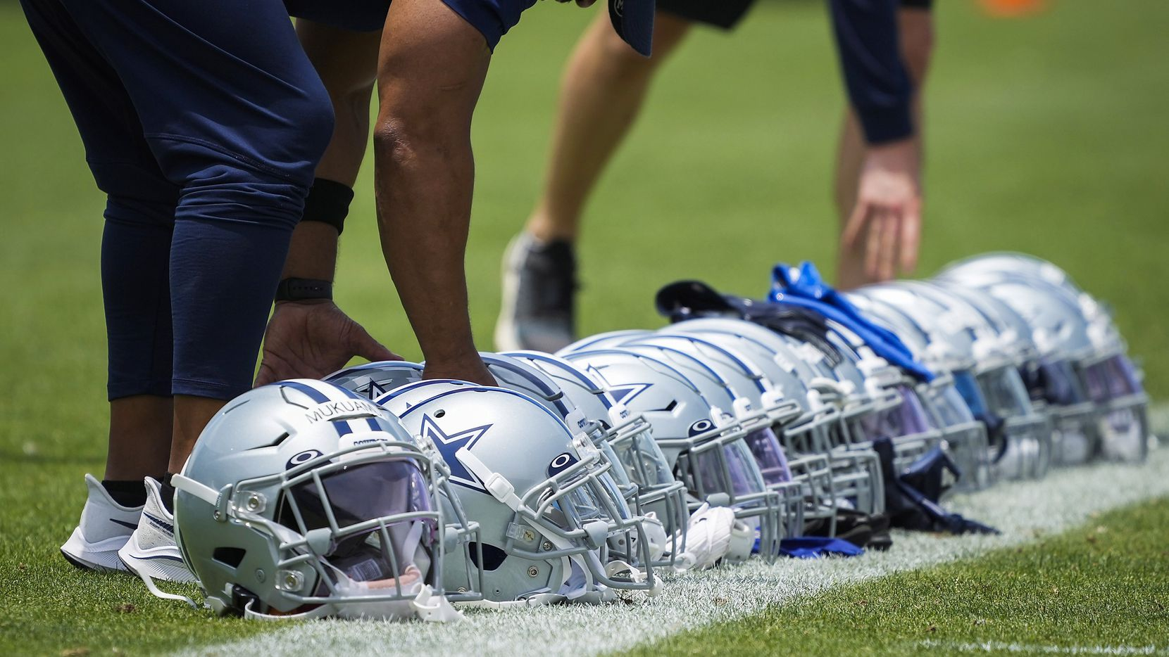 Dallas Cowboys staff line up defensive players helmets on the sideline during a minicamp practice at The Star on Tuesday, June 8, 2021, in Frisco.