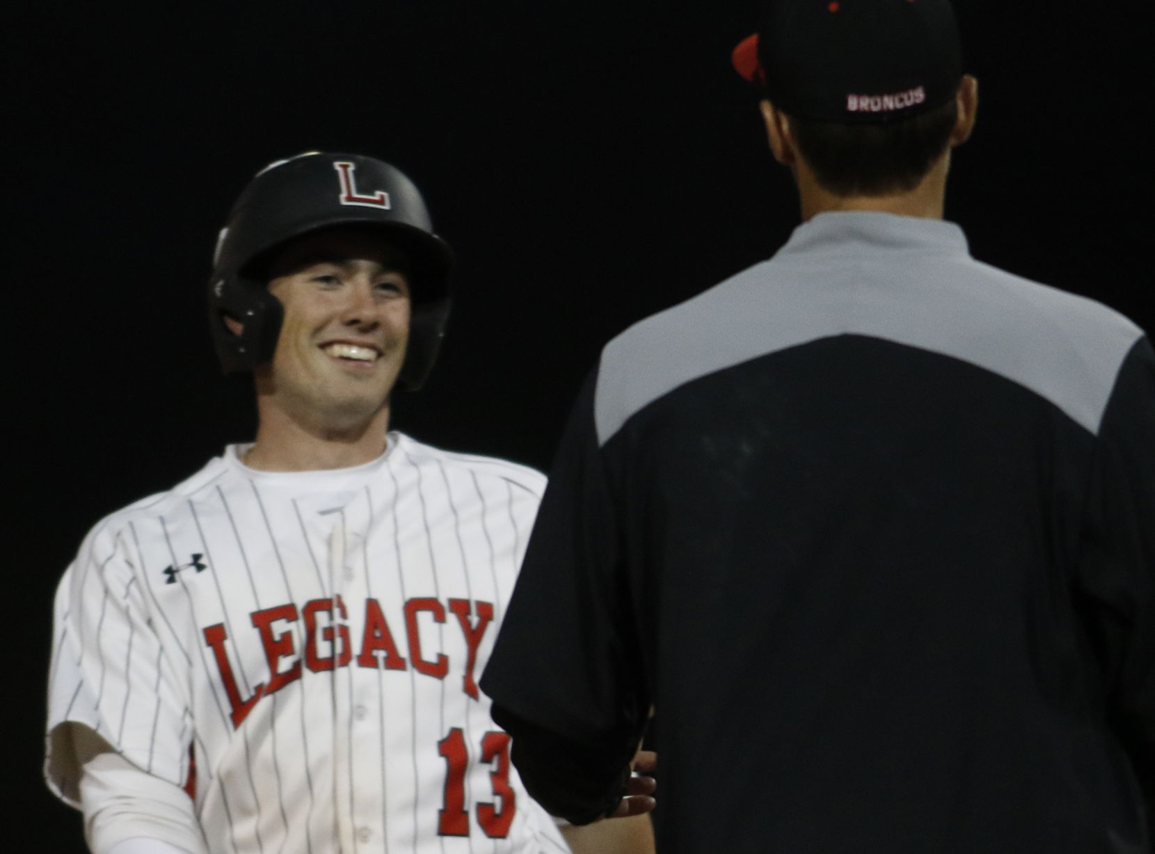 Mansfield Legacy infielder Nathan Rooney (13) was all smiles with head coach Chris McMullen after reaching second base with a double during third inning action against Arlington Sequin. Legacy defeated Sequin 16-0 in 5-innings. The two teams played their baseball game at Mansfield Legacy High School in Mansfield on March 19, 2019. (Steve Hamm/ Special Contributor)