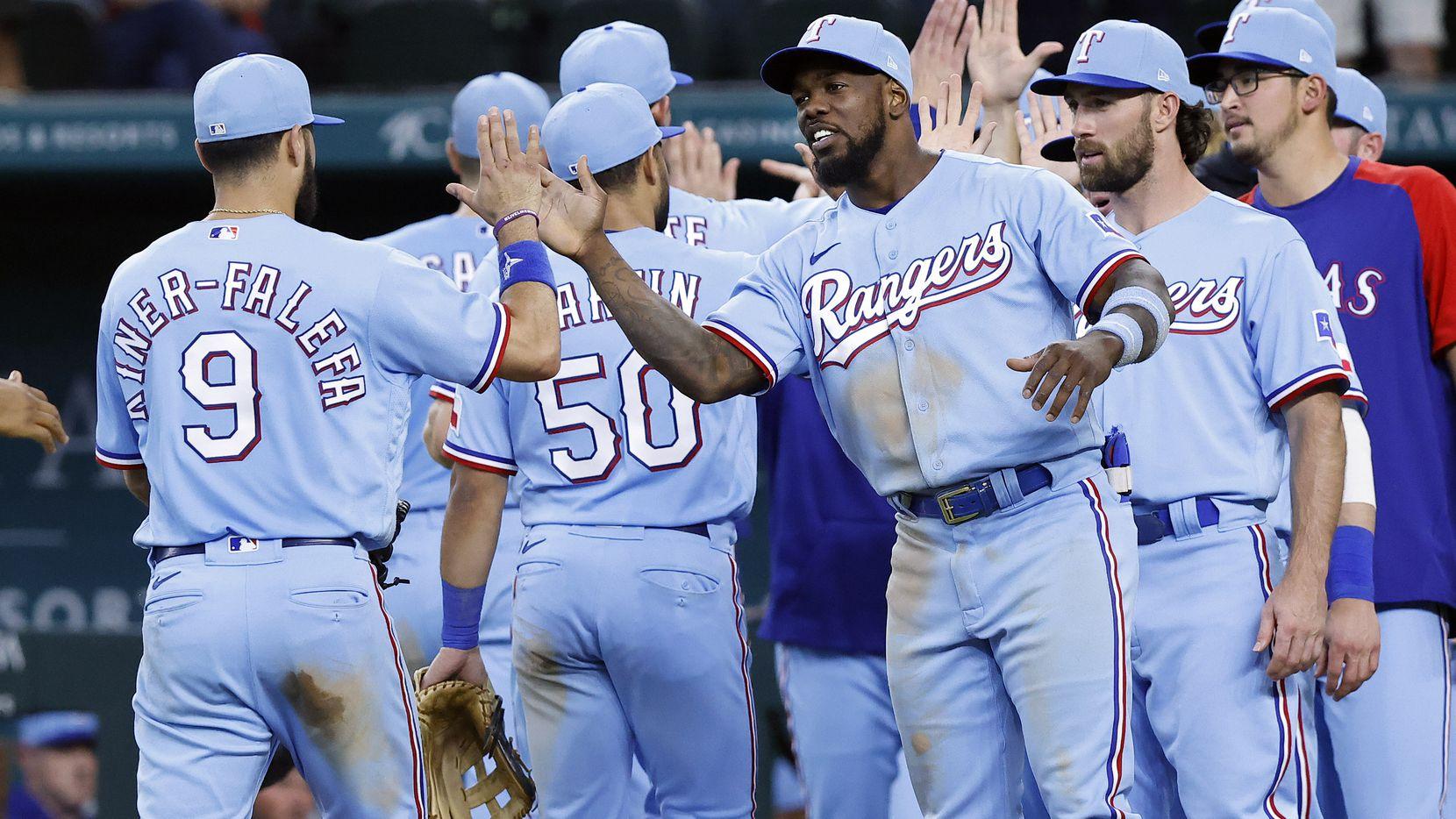 Texas Rangers right fielder Adolis Garcia (right) congratulates third baseman Isiah Kiner-Falefa (9) after their 4-1 win against the Kansas City Royals at Globe Life Field in Arlington, Texas, Friday, June 27, 2021.