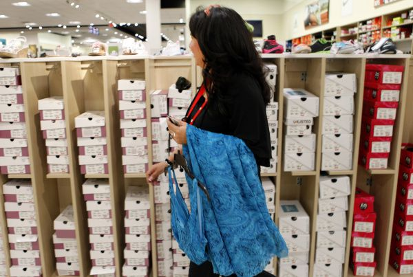 Shoe fit specialist Gloria Trevino uses her employee discount to shop for a dress during her break at J.C. Penney in Dallas.