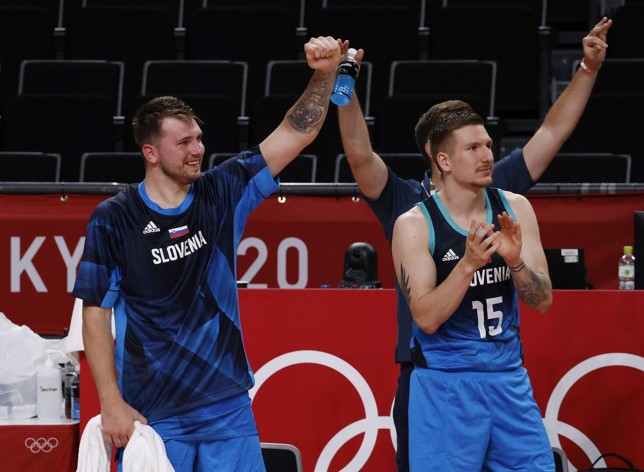 Slovenia's Luka Doncic (77), Gregor Hrovat (15) and teammates cheer on their team after a made basket in the second half of play against Argentina during the postponed 2020 Tokyo Olympics at Saitama Super Arena on Monday, July 26, 2021, in Saitama, Japan. Slovenia defeated Argentina 118-100. (Vernon Bryant/The Dallas Morning News)