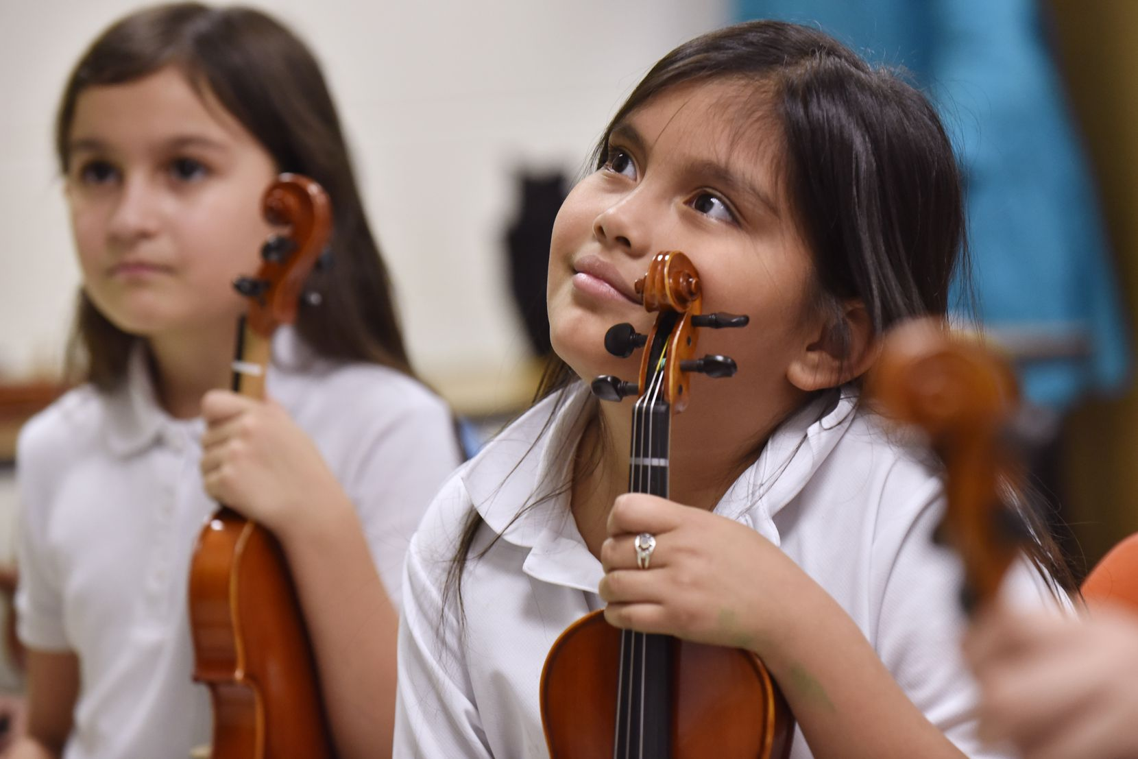 Mayte Mendoza, center, listens to instructions from teacher Nicole Melki. The 8-year-old says that the performances she and her classmates get to do is one of her favorite parts of violin lessons.