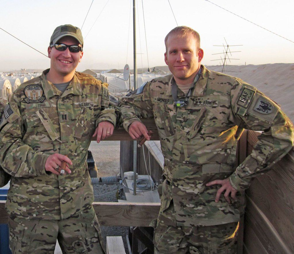 "Justin ""Buddy""  Lee (left) enjoys a cigar with fellow Chinook pilot Bryan Nichols at Forward Operating Base Shank, Afghanistan. Nichols was one of the pilots flying the Chinook shot down on Aug. 6, 2011."