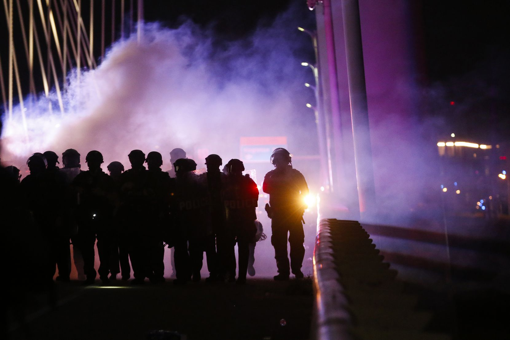 Police deploy crowd control chemical agents as they surround protesters who marched onto the Margaret Hunt Hill Bridge while demonstrating against police brutality on Monday, June 1, 2020, in Dallas. Hundreds of protesters were detained.