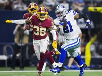 FILE — Dallas Cowboys running back Ezekiel Elliott (21) runs the ball ahead of Washington Football Team defensive back Jeremy Reaves (39) during the second quarter of an NFL game between the Dallas Cowboys and the Washington Football Team on Sunday, December 29, 2019 at AT&T Stadium in Arlington, Texas.