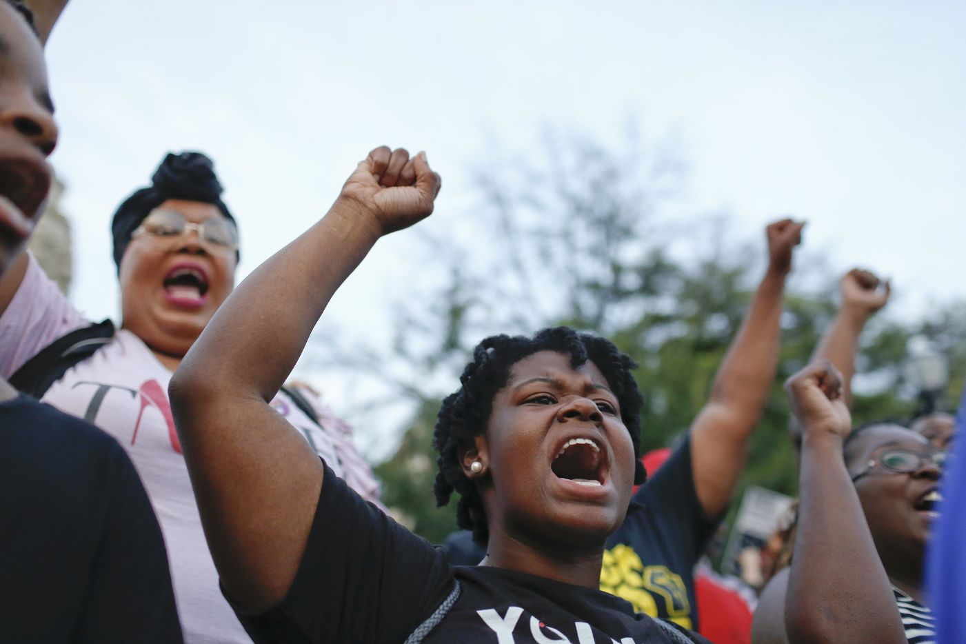 Kayla Smith, front, of Birmingham, Ala., chants during a solidarity rally Sunday, Aug. 13, 2017, in Birmingham for the victims of at a white supremacist rally that turned violent in Charlottesville, Va. Protesters decrying hatred and racism converged around the country Sunday, the day after the rally in  Charlottesville.