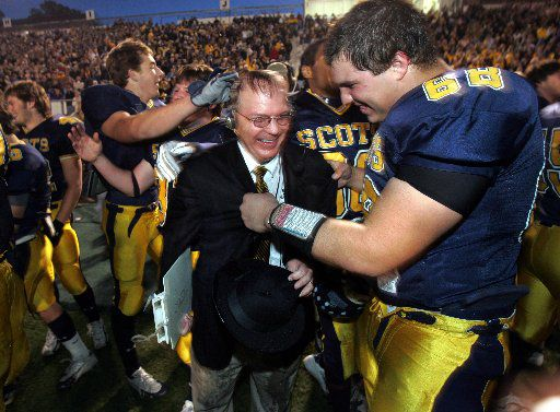 Highland Park coach Randy Allen gets consoled by Alex Cole (68 - right) after getting dunked with Gatorade after the Scots 59-0 victory in the 4A Division I State High School Football Championship game at the Rose Stadium in Tyler, TX on Saturday, December 10, 2005.
