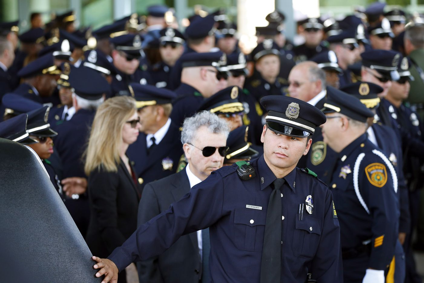 A Dallas police officer runs his hand over the back of the hearse after pallbearers loaded the flag draped casket of fallen Dallas police officer Lorne Ahrens at Prestonwood Baptist Church in Plano, Wednesday, July 12, 2016.
