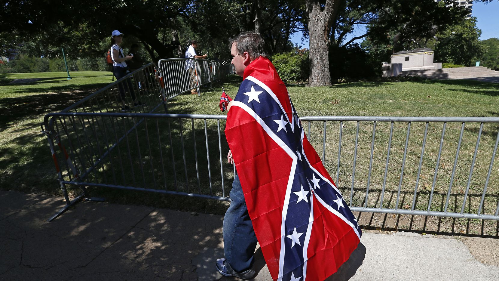 William Rutledge III, wrapped in a Confederate flag, walks on North Hall Street near the statue of Robert E. Lee at Robert E. Lee Park in Dallas on Thursday, Sept. 7, 2017.
