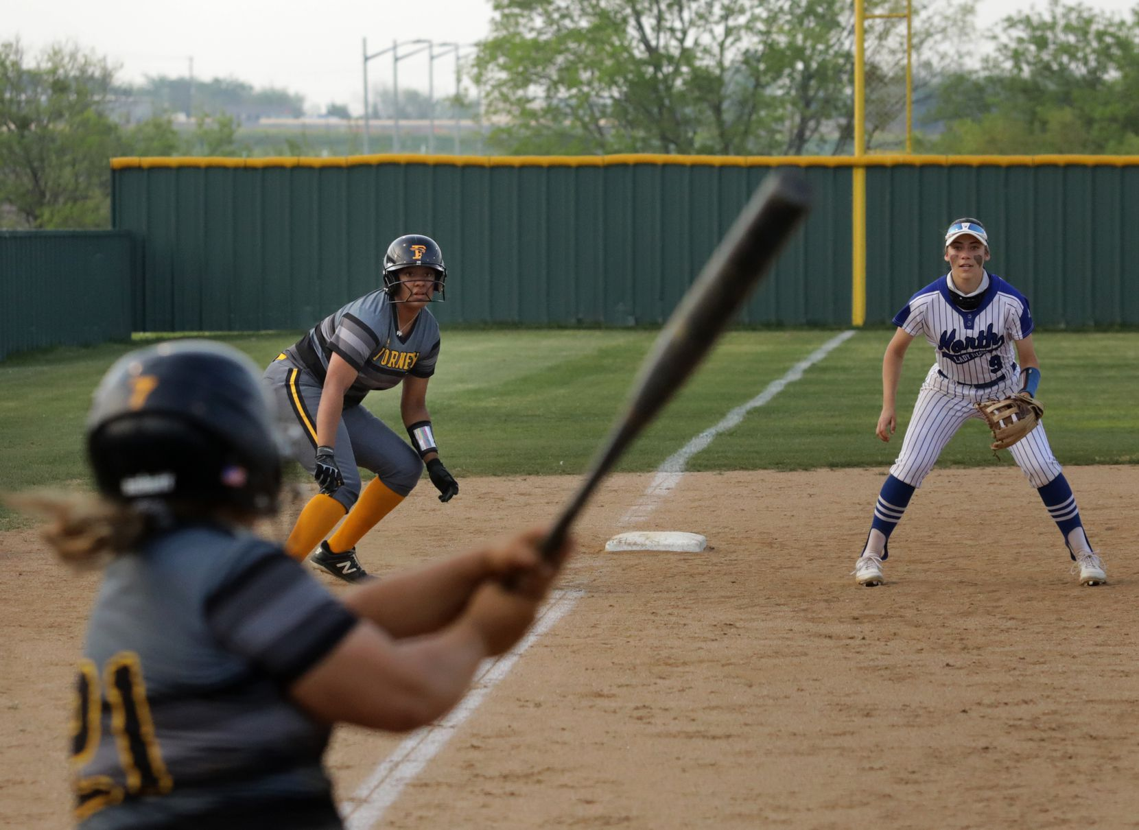 Vanessa Hollingsworth, center, prepares to run as Katie Kretz, left, swings for the ball during a softball game between Forney at North Forney at North Forney High School in Forney, TX, on Apr. 9, 2021. (Jason Janik/Special Contributor)