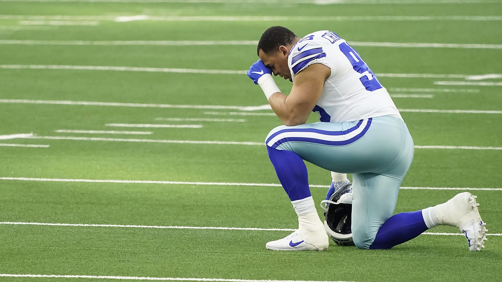 Dallas Cowboys defensive tackle Tyrone Crawford kneels in prayer before facing the Philadelphia Eagles in an NFL football game at AT&T Stadium on Sunday, Dec. 27, 2020, in Arlington.