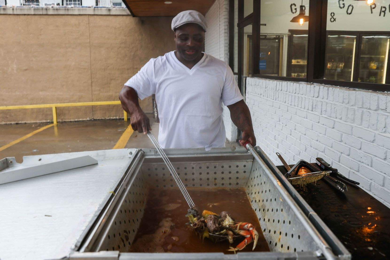 Eugene Vessel, owner of Sweet Grass Market, mixes up gumbo in front of the shop.