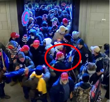 Capitol security video allegedly shows Garret Miller pushing his way into the building with others.