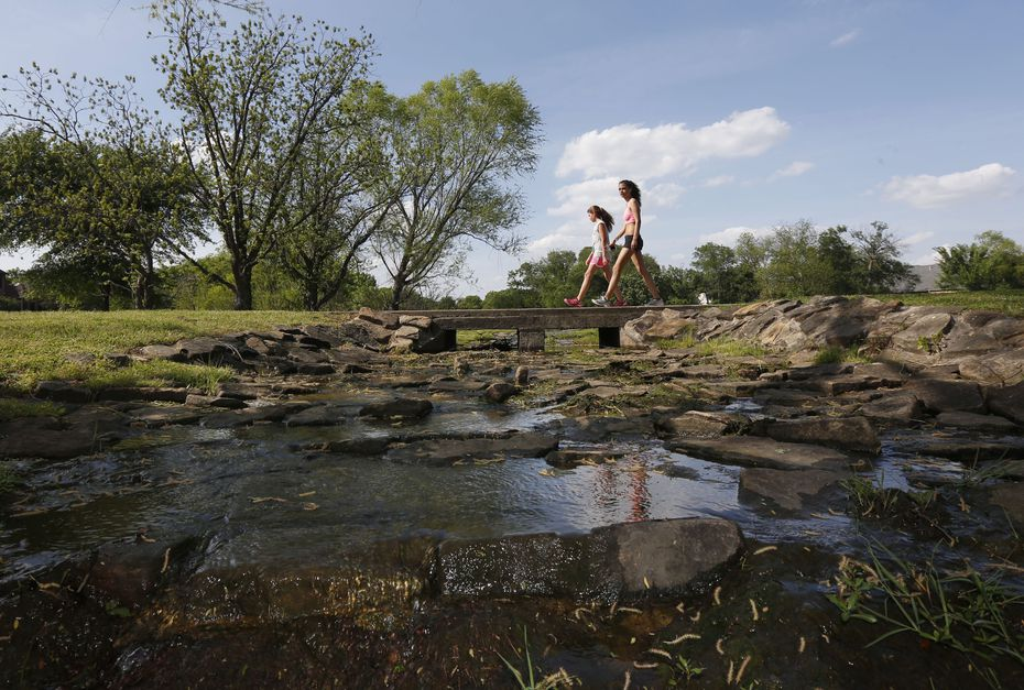 Two girls walk over a creek at the Colleyville Nature Center on April 23, 2014.