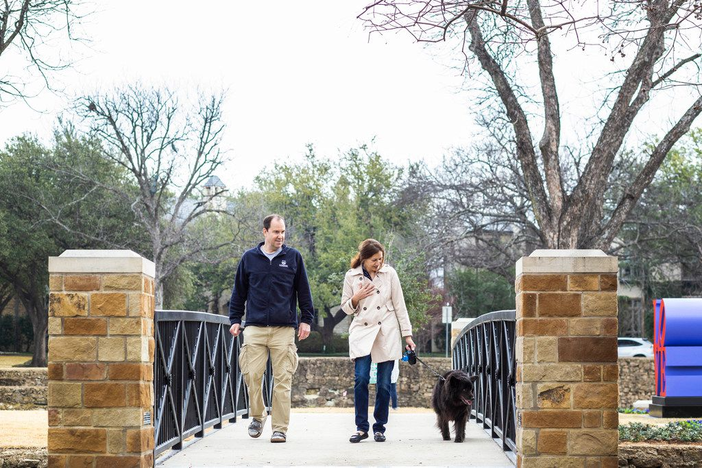 Ken and Alyssa Bohacs of Dallas walk with their dog Max at Williams Park in Dallas. The LOVE sculpture is off to the right.