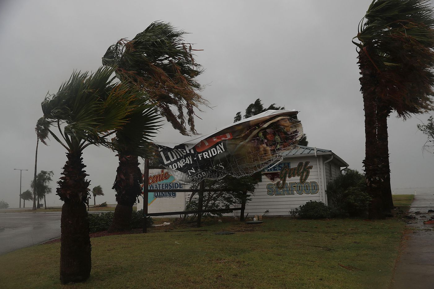 CORPUS CHRISTI, TX - AUGUST 25:  A sign blows in the wind after being partially torn from its frame by winds from Hurricane Harvey on August 25, 2017 in Corpus Christi, Texas.  Hurricane Harvey has intensified into a major hurricane and is aiming for the Texas coast with the potential for up to 3 feet of rain and 125 mph winds.