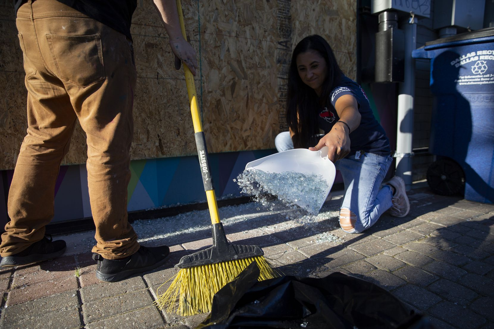 Reese Rodriguez helps clean glass from Upstairs Circus after being damaged during last night's protest, seen Saturday morning, May 30, 2020 in Dallas.
