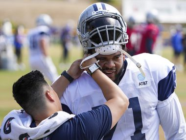 Dallas Cowboys tackle La'el Collins has his helmet worked on  during a joint practice with the Los Angeles Rams at training camp on Saturday, Aug. 7, 2021, in Oxnard, Calif.