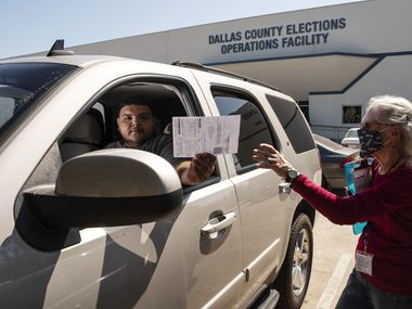 Volunteer Kathleen Campbell, 76, with the organization March to the Polls, reaches for the registration document from Jorge Hernandez, 23, after he registered to vote in Dallas County, outside of the Dallas County Elections Operations Facility in Dallas, Oct. 05, 2020.