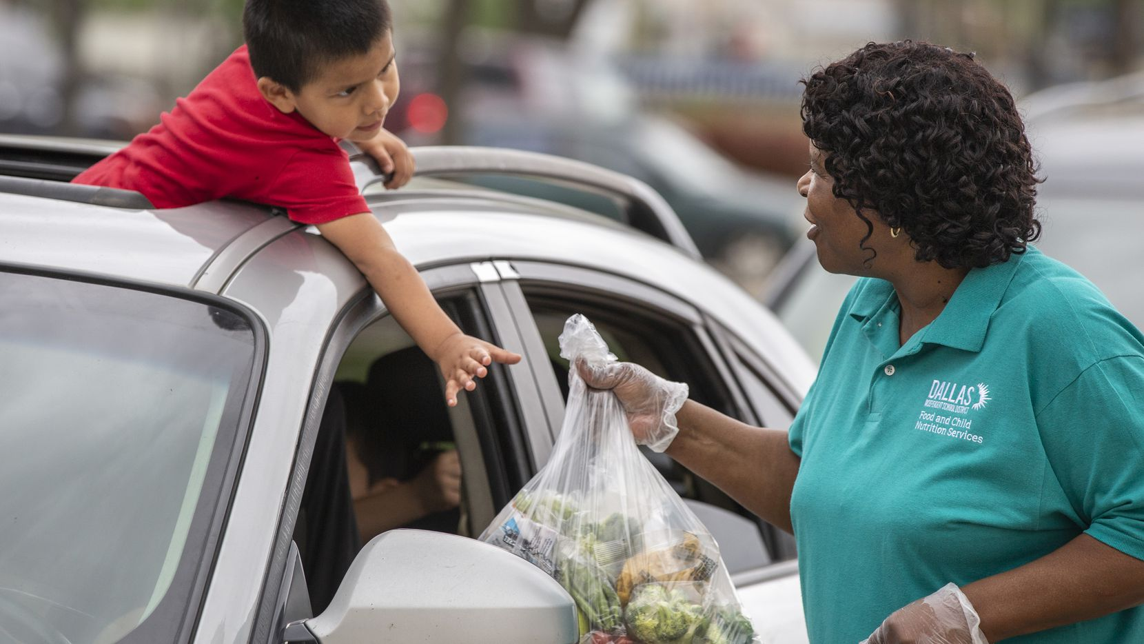 """As he hangs out of his family's car sunroof, Isaias Ovalle, 3, reaches for bagged school meals from food service supervisor Patricia Jackson (right) at Francisco """"Pancho"""" Medrano Middle School in Dallas on April 2, 2020. (Lynda M. Gonzalez/The Dallas Morning News)"""