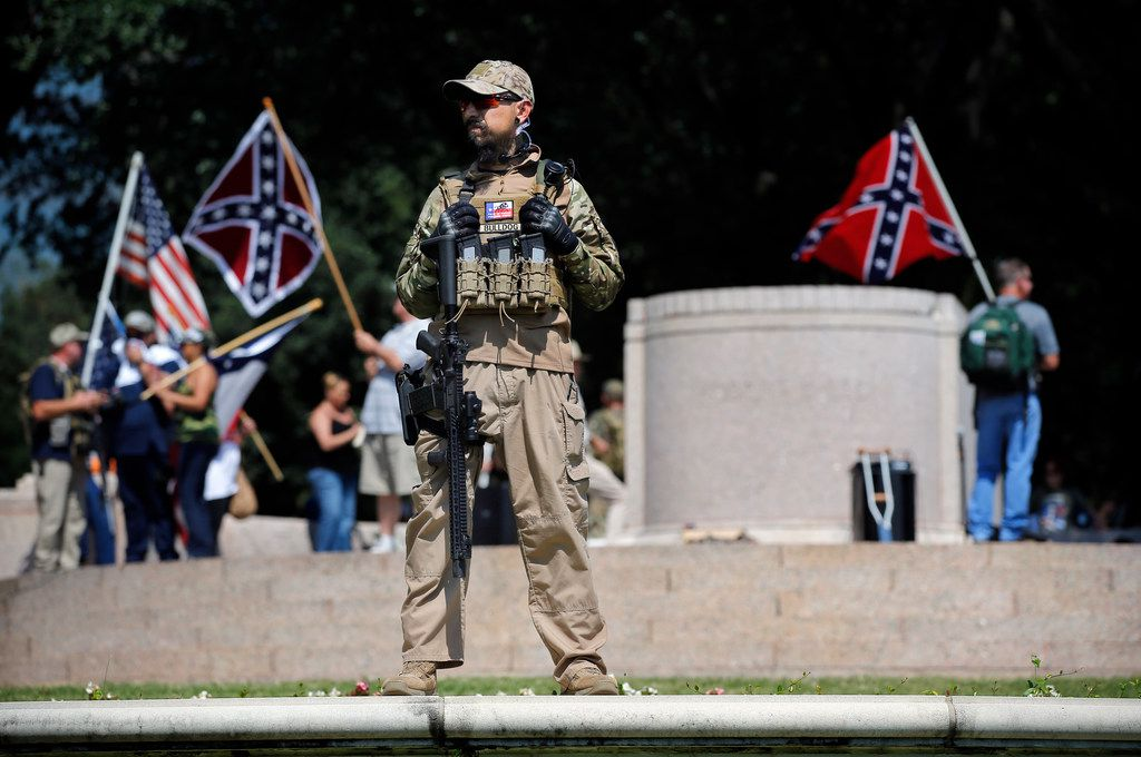 A Texas Liberty Coalition security person who goes by the name Bulldog stands guard over This Is Texas Freedom Force protest over removal of the Robert E. Lee statue from Lee Park in Dallas on Saturday.