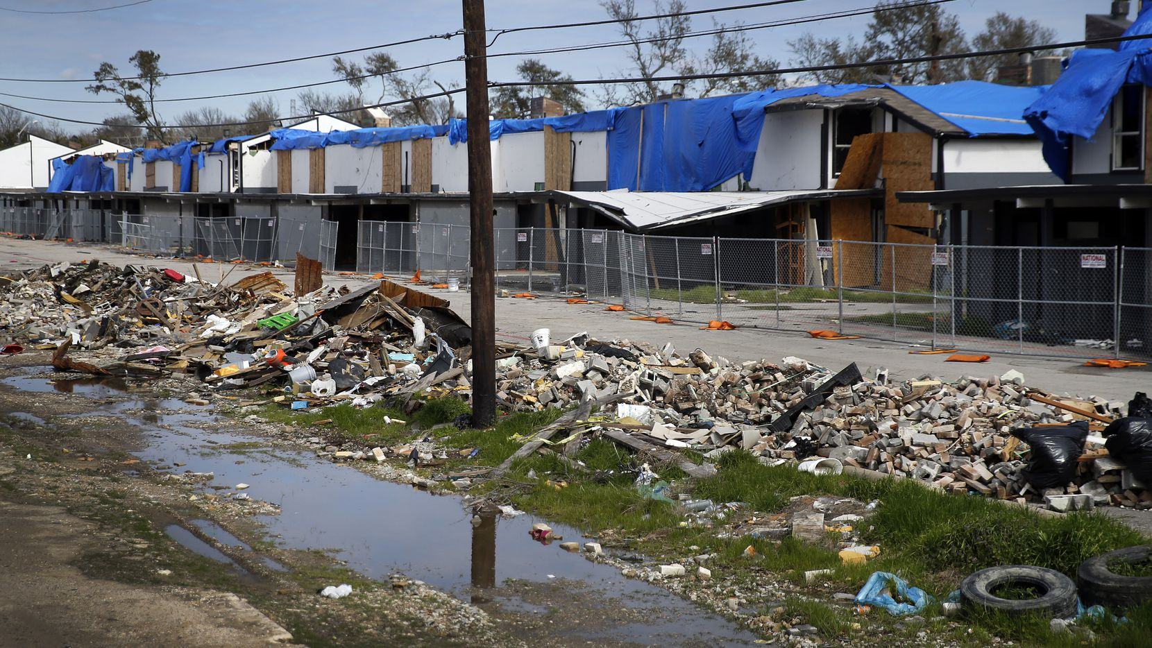 Four months after the tornado tore through northwest Dallas, the Southwind townhouse complex on Brockbank Drive still stands. Its residents have been scattered, making room for the homeless who have taken shelter amid the ruins.