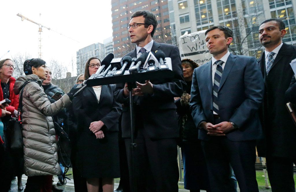Washington Attorney General Bob Ferguson talks to reporters as Solicitor General Noah Purcell, second from right, looks on Friday after a hearing in federal court in Seattle. A U.S. judge temporarily blocked President Donald Trump's ban on people from seven predominantly Muslim countries from entering the United States after Washington state and Minnesota urged a nationwide hold on the executive order that has launched legal battles across the country.