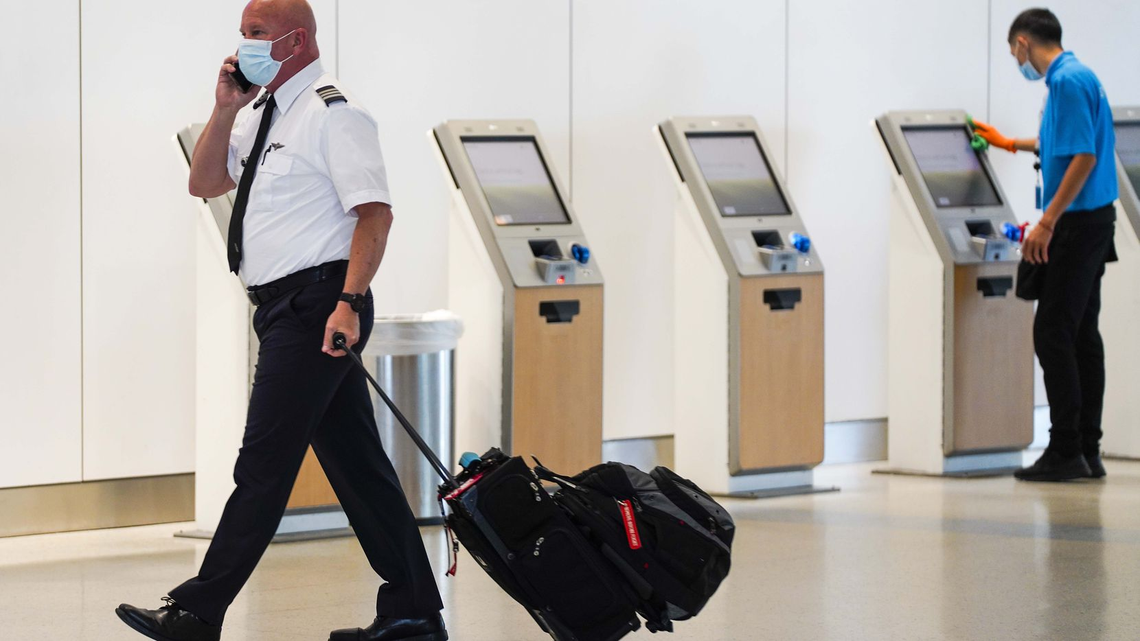 An American Airlines pilot walks past as airport contractor David Ramirez wipes down check in kiosks with disinfectant at Dallas Fort Worth (DFW) International Airport Terminal A on Tuesday, June 30, 2020, in Dallas. (Smiley N. Pool/The Dallas Morning News)