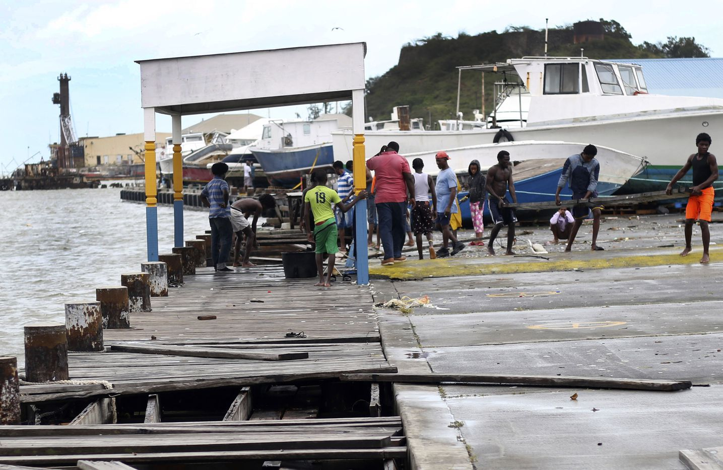 People recover broken parts of the dock after the passing of Hurricane Irma, in St. John's, Antigua and Barbuda, on Wednesday.