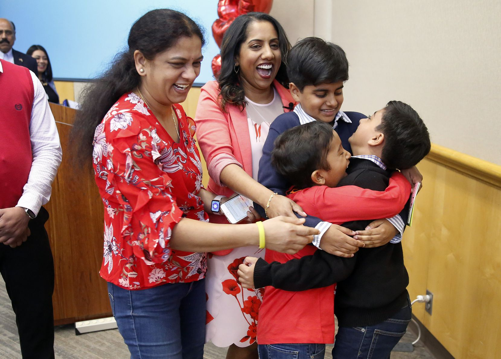 Bone marrow recipient Akshaj Nagilla (in red shirt, right) joins a group hug with his donor, Dr. Prasanthi Ganesa (back right), her kids Raghav, 12, and Revanth , 9 (right), and Akshaj's mother Anitha (left), Friday, February 14, 2020. Akshaj and his donor met for the first time after receiving her donation at Children's Medical Center Dallas.  (Tom Fox/The Dallas Morning News)
