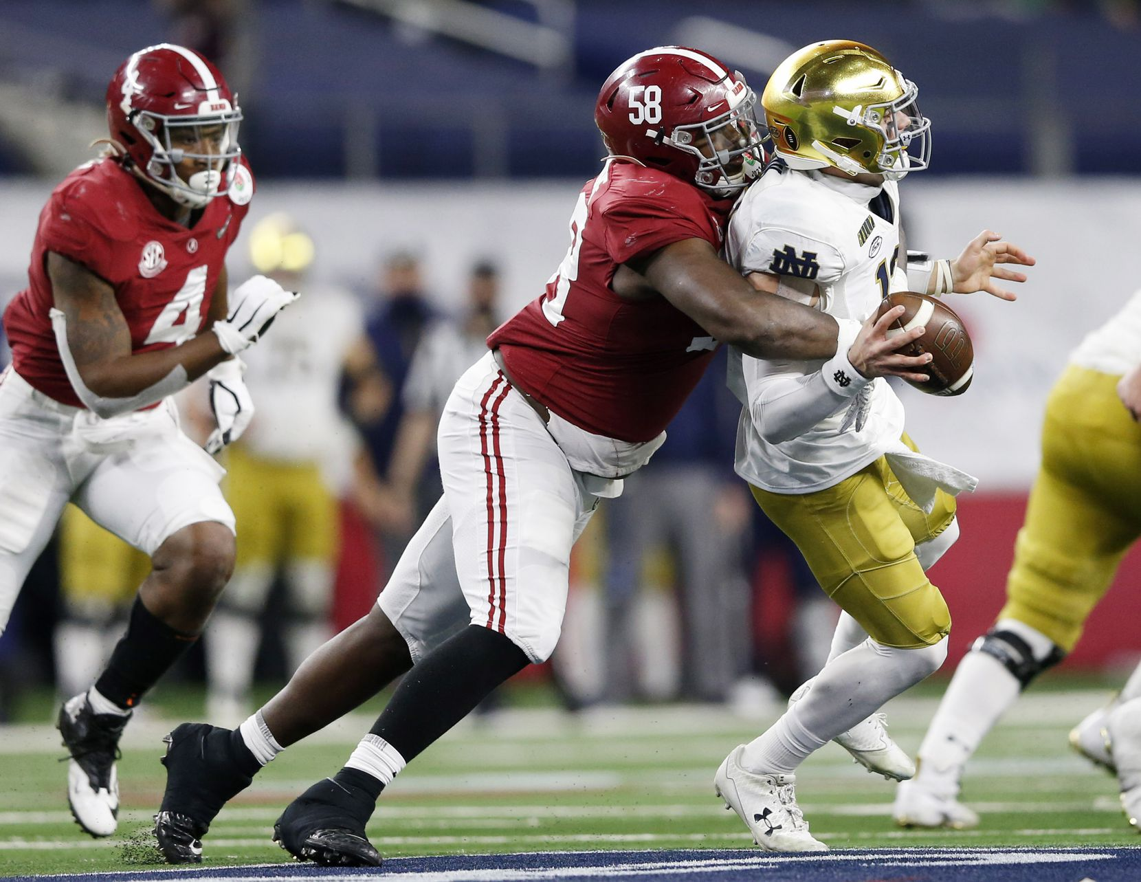Alabama Crimson Tide defensive lineman Christian Barmore (58) sacks Notre Dame Fighting Irish quarterback Ian Book (12) during the second half of play at the Rose Bowl NCAA college football playoff semifinal at AT&T Stadium on Friday, December 30, 2020 in Arlington, Texas. Alabama Crimson Tide defeated Notre Dame Fighting Irish 31-14. (Vernon Bryant/The Dallas Morning News)
