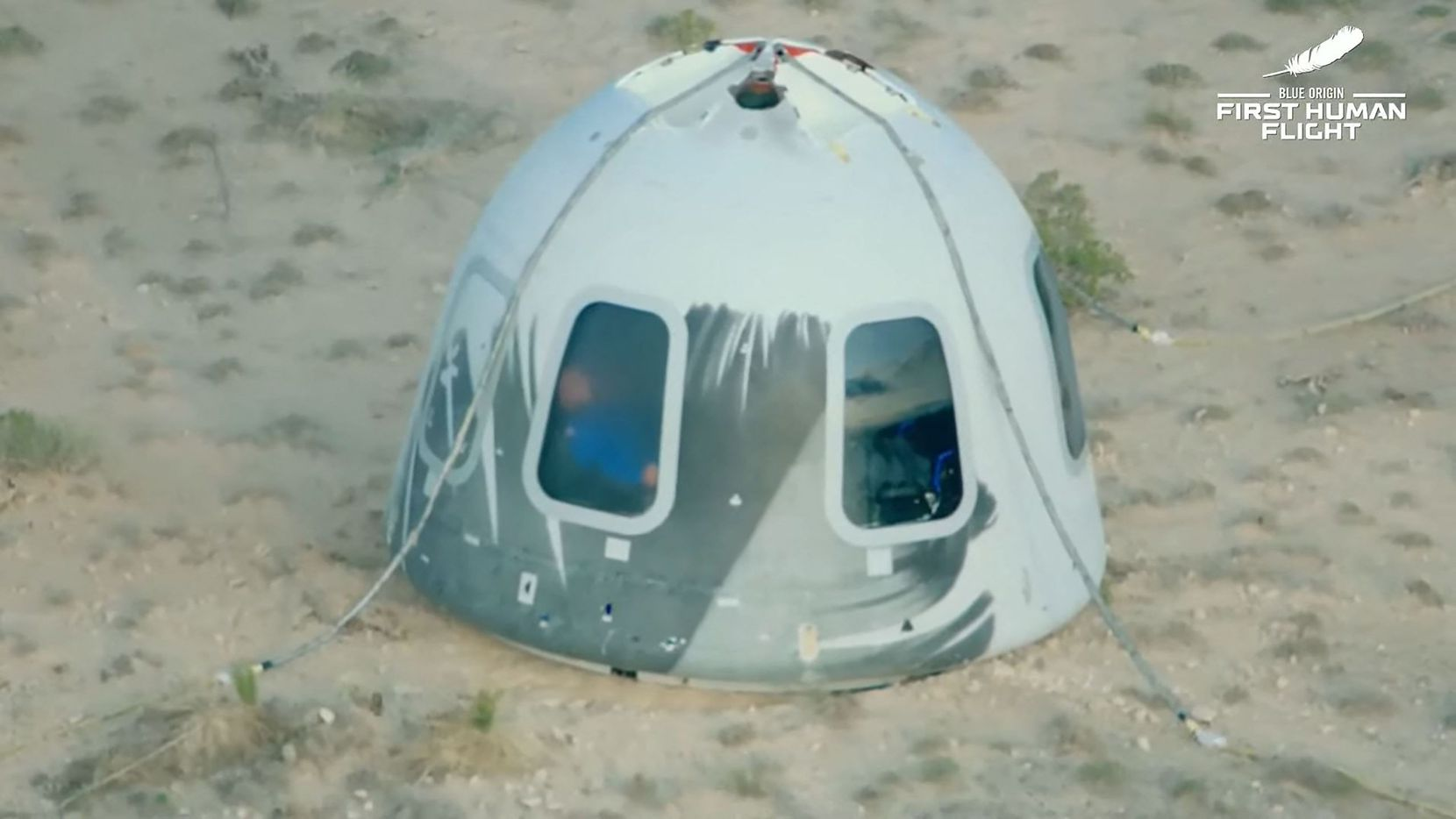 """This still image taken from video by Blue Origin shows Blue Origin's reusable New Shepard craft capsule as it returns from space after it safely landed, on July 20, 2021, in Van Horn, Texas. - Blue Origin's first crewed mission is an 11-minute flight from west Texas to an altitude of 65 miles (106kms), and back again, to coincide with the 52nd anniversary of the first Moon landing. (Photo by Handout / BLUE ORIGIN / AFP) / RESTRICTED TO EDITORIAL USE - MANDATORY CREDIT """"AFP PHOTO / Blue Origin"""" - NO MARKETING - NO ADVERTISING CAMPAIGNS - DISTRIBUTED AS A SERVICE TO CLIENTS (Photo by HANDOUT/BLUE ORIGIN/AFP via Getty Images)"""