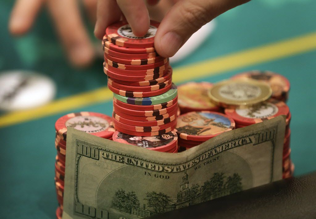 A poker player takes his ante from his stack of chips during a game of Texas Hold 'Em.