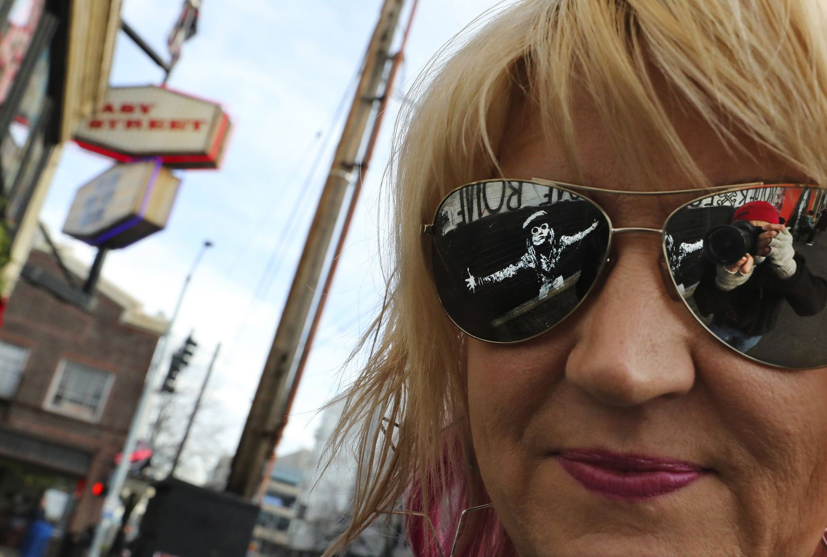 Photographer and author Karen Mason Blair's sunglasses reflect the late Andrew Wood of rock band Mother Love Bone. Wood is featured in one of the murals outside Easy Street Records in Seattle.