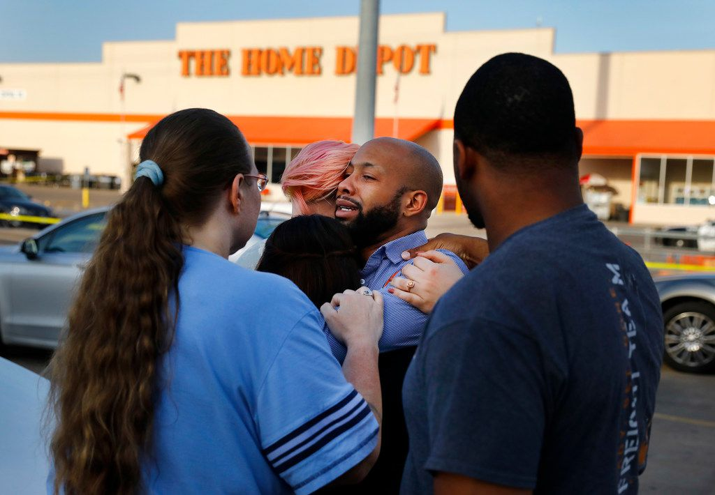 Home Depot employees comfort each other outside the Dallas store after two officers and a civilian were shot by a man on Tuesday.