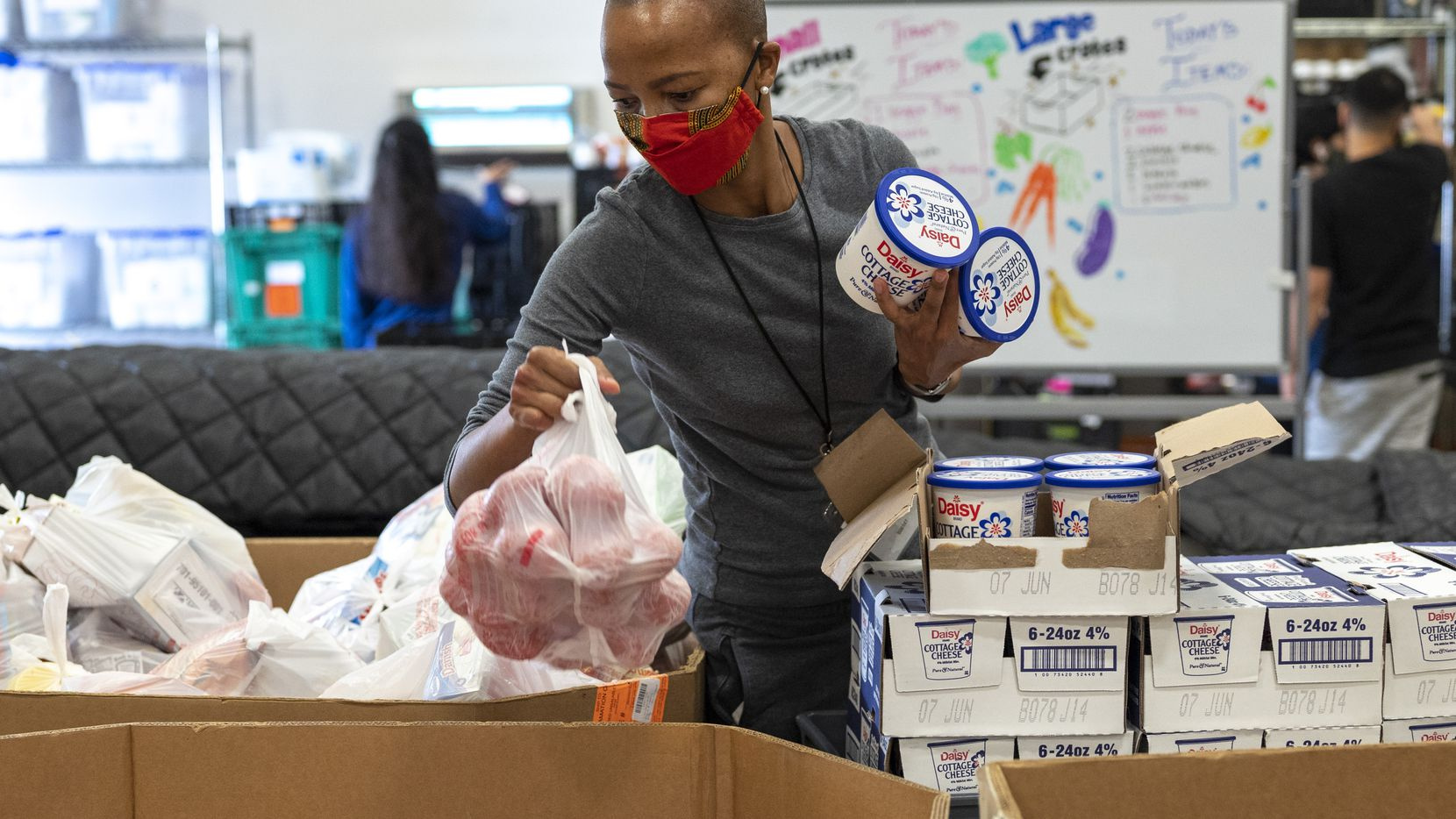 """Volunteer Dineo Gaofhiwe-Ingram gathers items like cottage cheese and fruits to pack in boxes for families in need at Crossroads Community Services in South Dallas. """"I wanna help and make a difference because there's a need,"""" she says. """"That's really why I'm doing it. Just to help."""""""