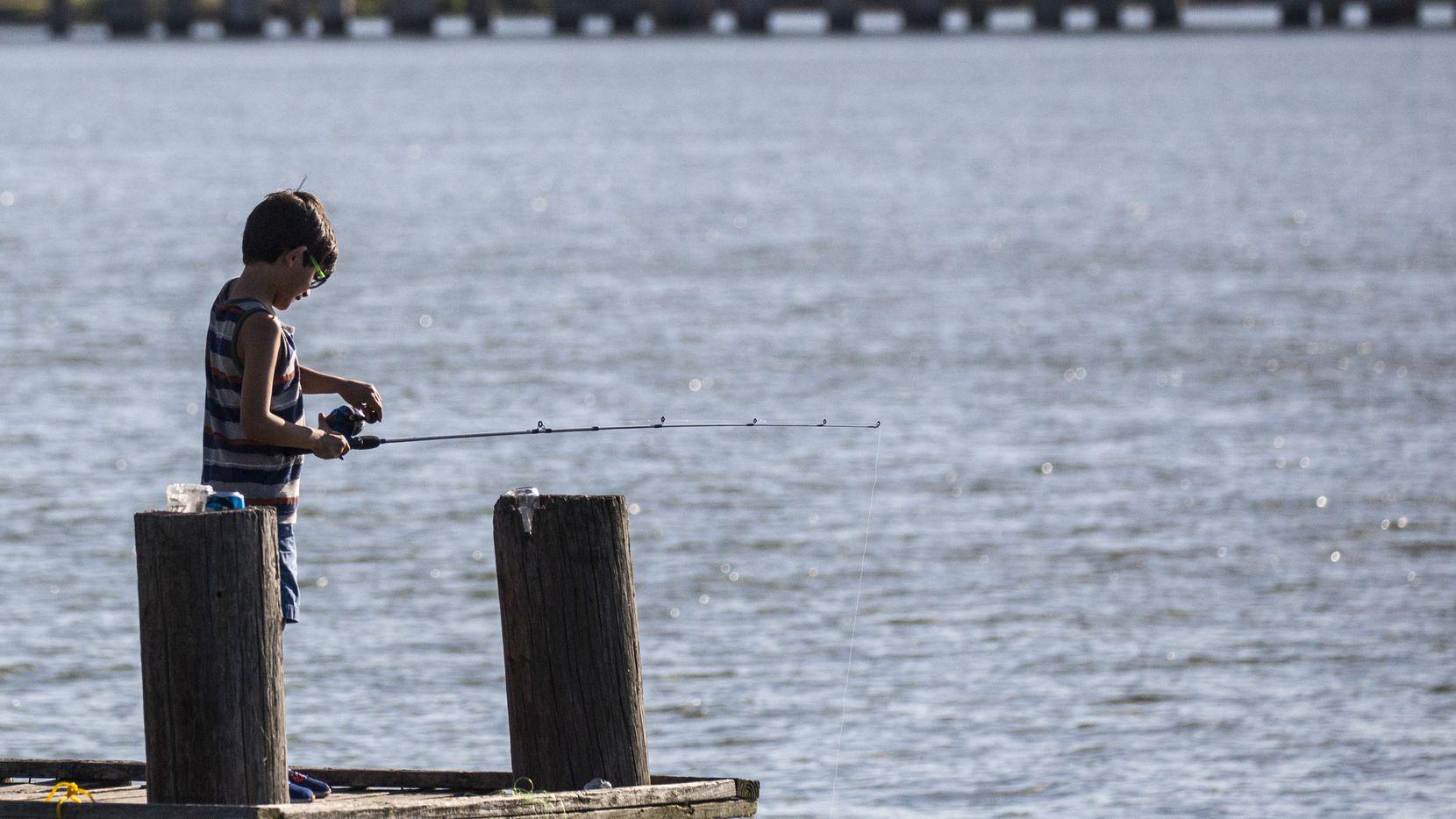 Jovanni Ledezma, 7, fishes from a pier at John Paul Jones Park along Lake Ray Hubbard in Garland, Texas, on Saturday, July 18, 2020.