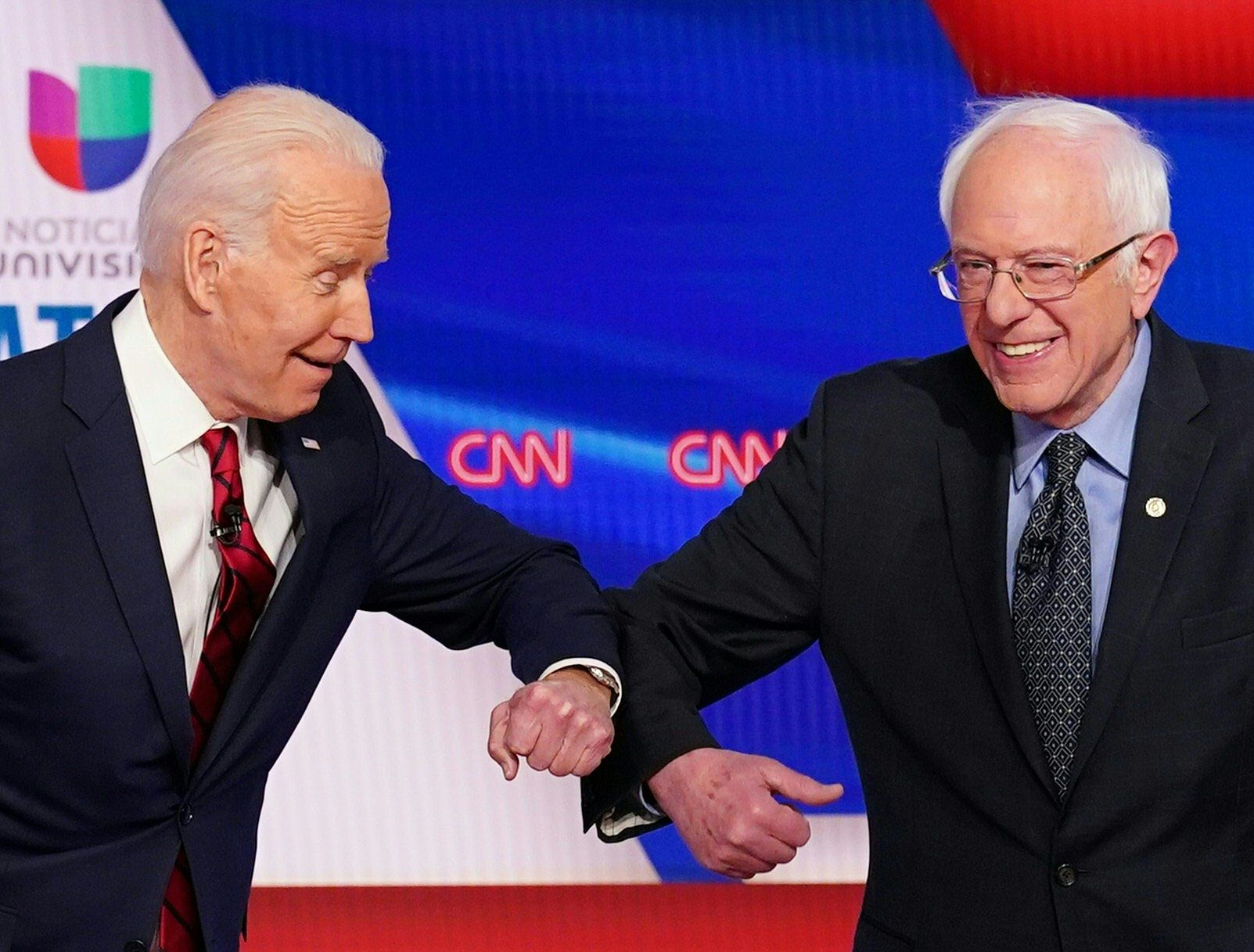 In this file photo taken on March 15, 2020 Democratic presidential hopefuls former vice president Joe Biden (L) and Senator Bernie Sanders greet each other with a safe elbow bump before the start of the 11th Democratic Party 2020 presidential debate in a CNN Washington Bureau studio.