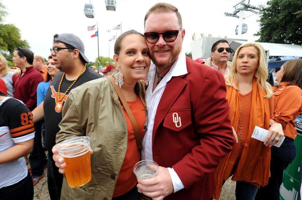 Laura Cunningham and Oklahoma University alumni Chris Fields hold beers outside the Cotton Bowl in 2014. At this year's Texas-OU game, of-age fans can buy beer at more than 20 stands inside the stadium.