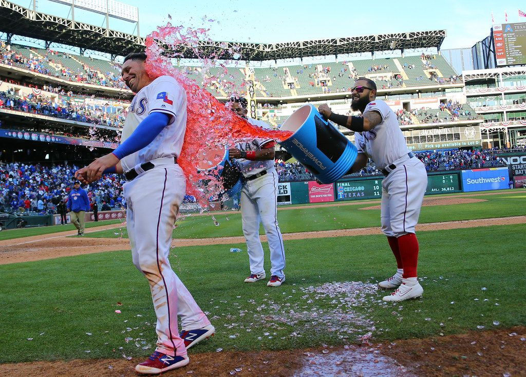 ARLINGTON, TX - MARCH 31: Elvis Andrus #1 of the Texas Rangers and Rougned Odor #12 dump the coolers of water on Asdrubal Cabrera #14 celebrating the win against the Chicago Cubs at Globe Life Park in Arlington on March 31, 2019 in Arlington, Texas. (Photo by Rick Yeatts/Getty Images)