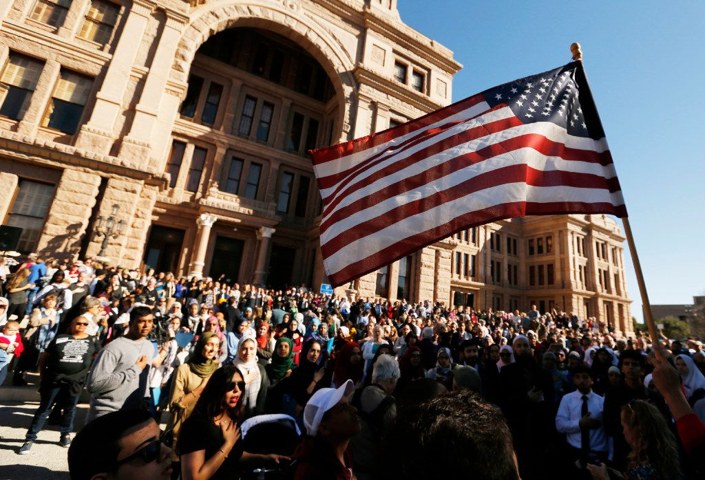 People gather as the national anthem is sung during a press conference at the steps of the Texas Capitol during the Texas Muslim Capitol Day rally in Austin on Tuesday, Jan. 31, 2017.