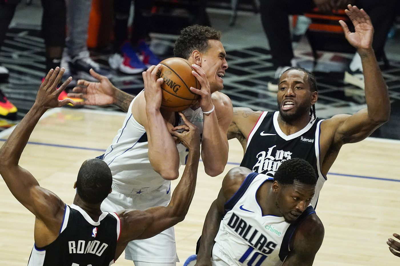 Dallas Mavericks center Dwight Powell (7) grabs a rebound from LA Clippers guard Rajon Rondo (4) and forward Kawhi Leonard (2) during the third quarter of an NBA playoff basketball game at the Staples Center on Wednesday, June 2, 2021, in Los Angeles.  (Smiley N. Pool/The Dallas Morning News)