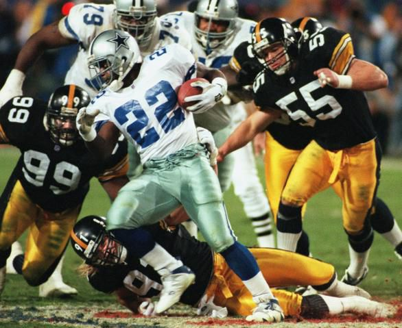 Dallas Cowboys running back Emmitt Smith (22) eludes Pittsburgh Steelers linebackers Levon Kirkland and Kevin Greene (on ground) in the third quarter of Super Bowl XXX at Sun Devil Stadium in Tempe Arizona, on Jan. 28, 1996.