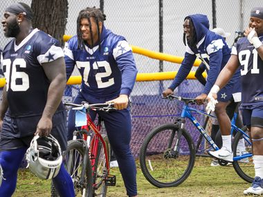Dallas Cowboys defensive end DeMarcus Lawrence (90) and defensive tackle Trysten Hill (72) ride bicycles as they leave the field following a practice at training camp on Saturday, July 24, 2021, in Oxnard, Calif.