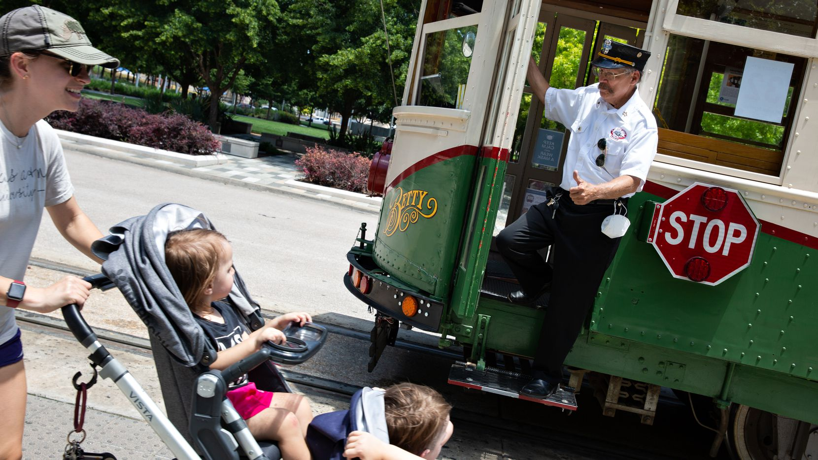 """John Landrum, vice president of operations, systems and technology for the McKinney Avenue Transit Authority, gives the thumbs-up to kids passing by """"Betty,"""" one of the Dallas agency's streetcars. on Wednesday, May 25,2021."""