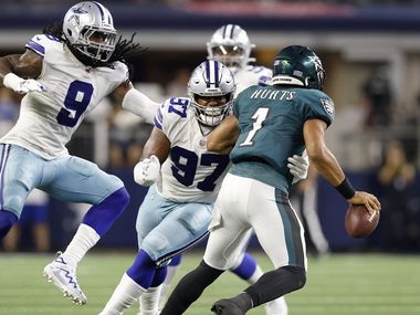 Dallas Cowboys defensive tackle Osa Odighizuwa (97) wraps up Philadelphia Eagles quarterback Jalen Hurts (1) for a fourth quarter sack at AT&T Stadium in Arlington, Monday, September 27, 2021. Middle linebacker Jaylon Smith (9) joined in on the defensive play. The Cowboys won, 41-21.