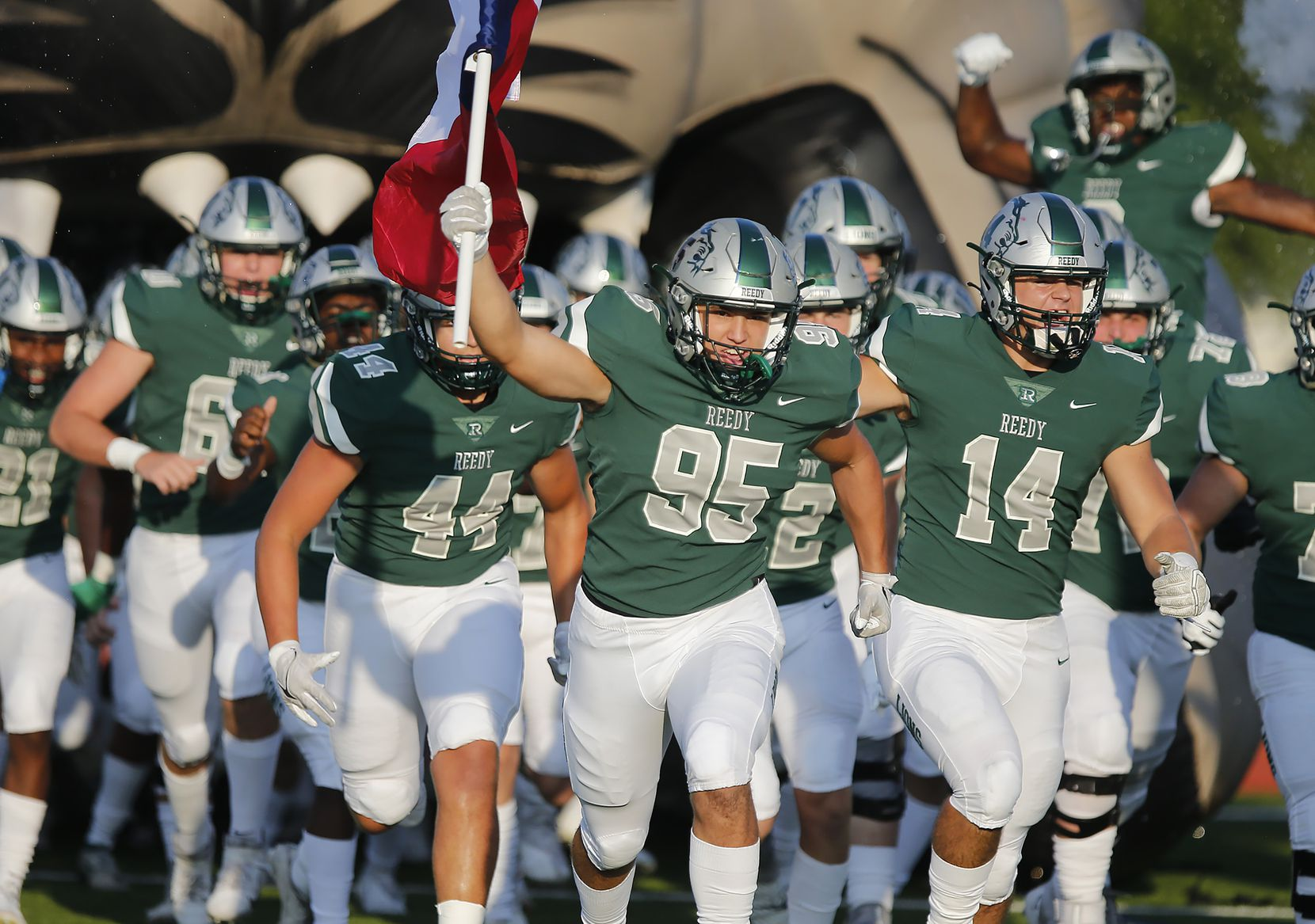 Reedy defensive tackle Chase Miller (95) leads his team onto the field holding the Texas flag before kickoff as Reedy High School hosted Frisco Liberty High School at David Kuykendall Stadium in Frisco on Wednesday night, August 26, 2021. (Stewart F. House/Special Contributor)
