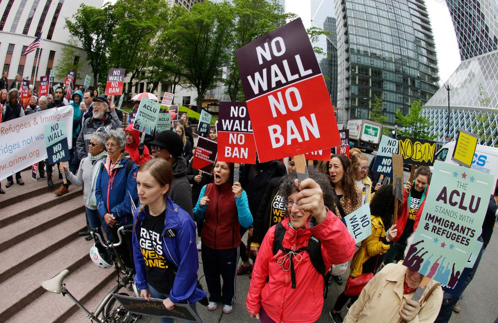 FILE - In this May 15, 2017 file photo, protesters wave signs and chant during a demonstration against President Donald Trump's revised travel ban, outside a federal courthouse in Seattle. The Supreme Court is letting the Trump administration enforce its 90-day ban on travelers from six mostly Muslim countries, overturning lower court orders that blocked it. The action Monday, June 26, 2017, is a victory for President Donald Trump in the biggest legal controversy of his young presidency. (AP Photo/Ted S. Warren, File)